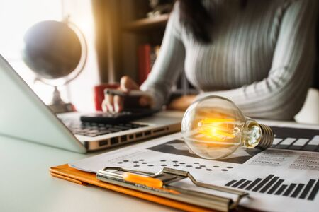 Photo pour light bulb with business hand working with tablet, laptop computer and creative business strategy in morning light - image libre de droit