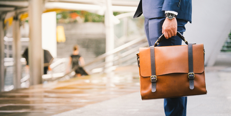 Foto de Closeup Of A Businessman wear the watch and Holding leather Briefcase Going To Work with the sunshine - Imagen libre de derechos