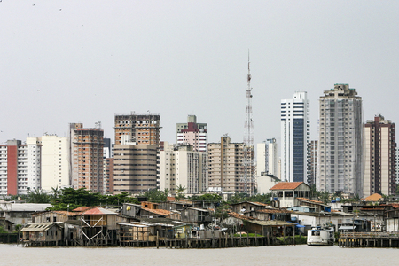 Photo for Belem: Modern buildings and stilt houses on the Guama river. Stark contrast to the social inequality between wealth and poverty - Royalty Free Image