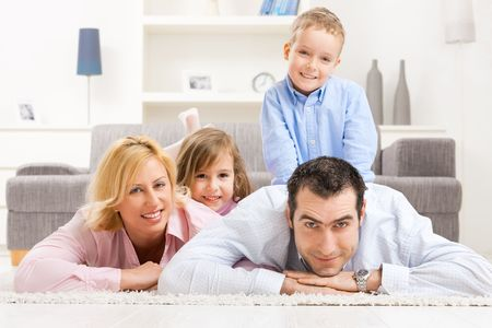 Portrait of happy family lying heaped on floor in living room, smiling.