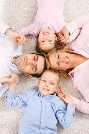 Portrait of happy family lying on carpet with their heads close together, smiling.