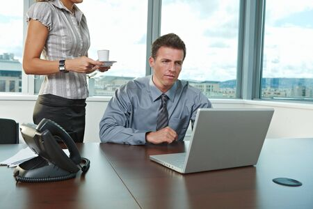 Secretary serving coffee. Businessman working on laptop computer at office.
