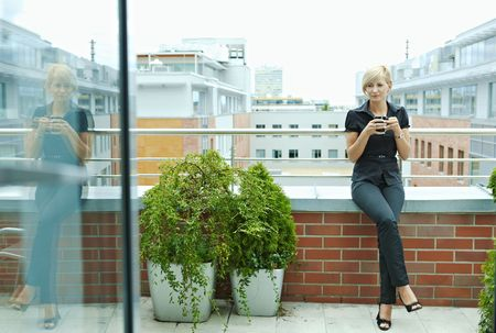 Businesswoman having break on office terrace outdoor drinking coffee.