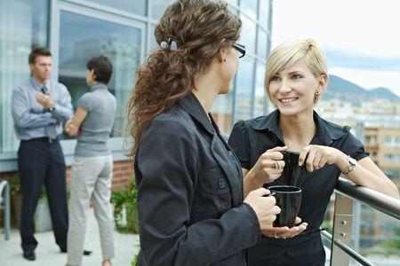 Businesswomen having break on office terrace outdoor drinking coffee talking.