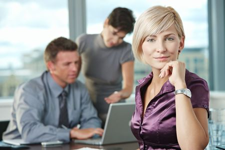 Smiling businesswoman on business meeting at office with team in background.