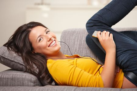 Happy teen girl lying on sofa at home listening music on earphones, smiling.