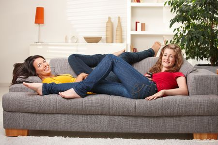 Happy teen girls lying on sofa together smiling at camera having rest at home.