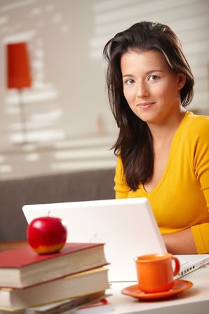 Teen student looking at camera smiling sitting at table with laptop computer.