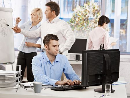 Casual businessman sitting at office desk, working on computer. Businesspeople working in background.