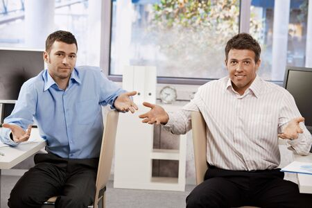 Two businessmen sitting at office looking at the camera confused, speading hands.
