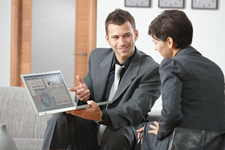 Smiling young businessman presenting on laptop computer sitting on sofa at office.