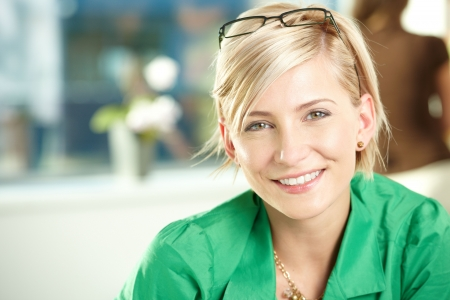 Closeup portrait of attractive young businesswoman wearing green shirt, smiling.