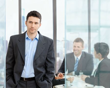 Young businessman standing in modern glass office, businesspeople having a meeting in the background.