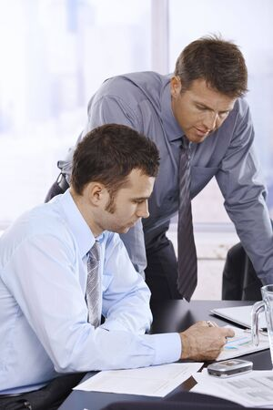 Mid-adult businessmen working together in office.