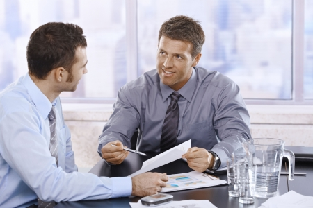 Happy businessmen discussing business report sitting at meeting table in office.