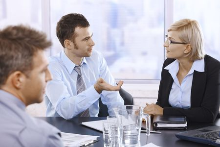 Businessman talking to businesswoman at business meeting in office.