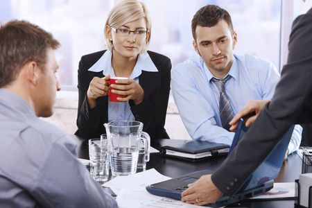 Business team at discussion, looking at laptop, businesswoman drinking coffee looking at screen.