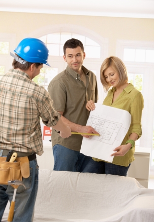 Smiling couple discussing ground plan of new home with builder.