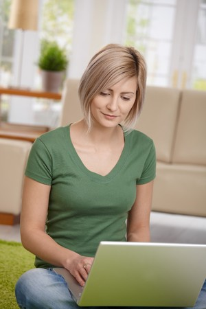 Blond woman sitting on floor at home in living room using laptop computer for browsing internet.