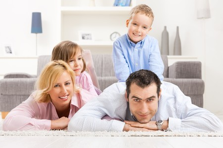Portrait of happy family lying together on floor in living room, smiling.