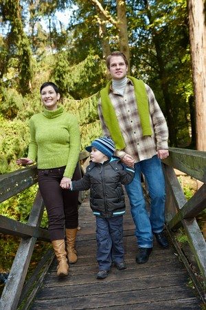 Happy family walking on bridge in autumn forest together, smiling, holding hands.