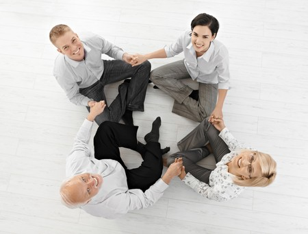 Smiling businessteam doing relaxation, looking at camera sitting on floor in lotus posture, high angle view.