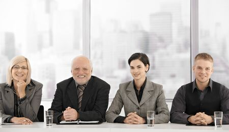 Formal businessteam portrait of different generations sitting at meeting table, smiling at camera.