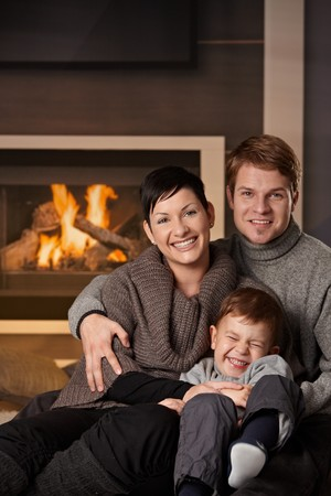 Happy family sitting on couch at home in a cold winter day, looking at camera, laughing.