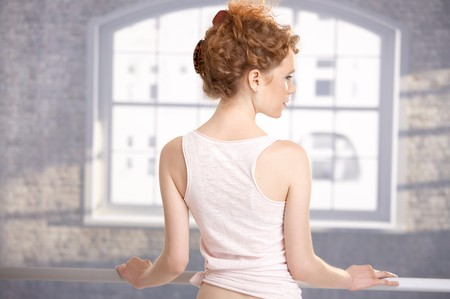 Young girl standing by bar in dance studio front of window showing her back.