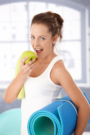 Pretty girl biting an apple after exercising in gym.