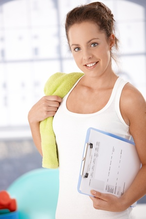 Pretty young girl prepared for personal training in gym, holding her training plan in hand.