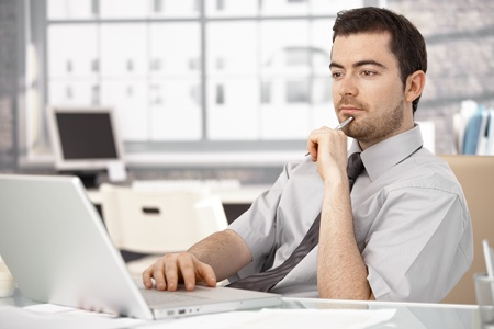 Young businessman working in bright office, sitting at desk, using laptop.