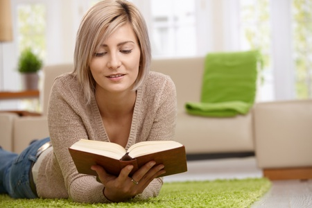 Young blonde woman relaxing on floor at home reading book. Copyspace on right.