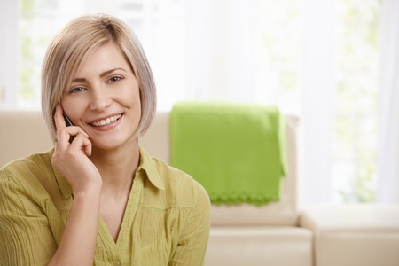 Portrait of attractive young woman speaking on mobile phone at home, smiling at camera.