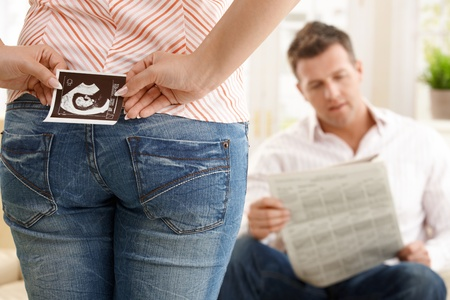 Woman hiding ultrasound picture of baby behind back standing in front of man reading newspaper on couch.