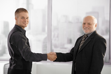 Portrait of senior executive shaking hands with young employee, looking at camera, smiling.