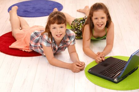 Portrait of smiling small girls lying on floor using laptop computer at home, looking at camera.
