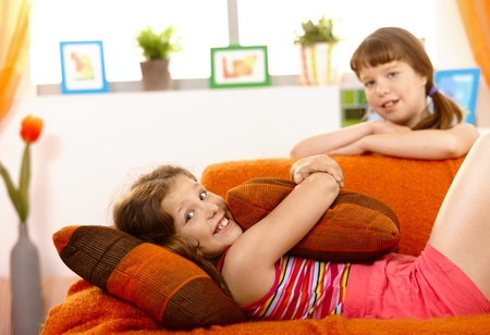 Cute small girl relaxing on sofa, smiling, hugging pillow, friend in background.