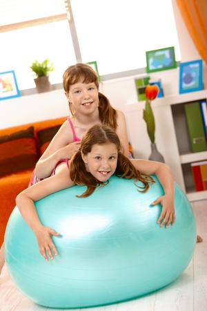 Small girls playing with gym ball in living room, smiling at camera.