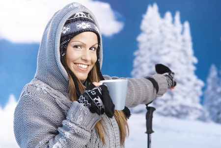 Attractive young female skiing, resting, drinking hot tea, pointing to winter landscape, smiling.