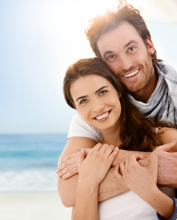 Happy young couple embracing on summer beach, having fun together, laughing.