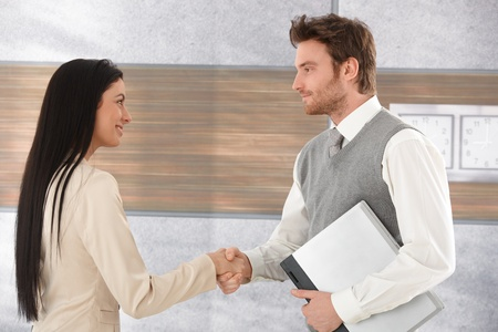 Young businesspeople greeting each other by shaking hands, smiling.