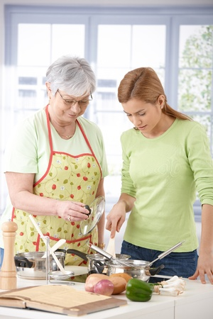 Senior mother and daughter cooking together in kitchen.