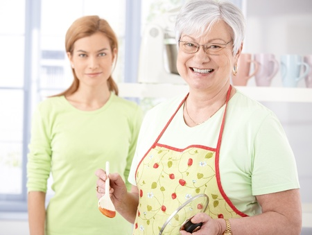 Cheerful senior mother cooking in kitchen, daughter watching from background.