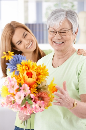 Elderly woman and daughter smiling happily at mother's day, having flowers.