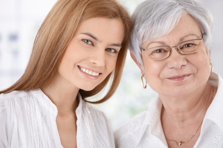Closeup portrait of young attractive woman and senior mother, both smiling, looking at camera.