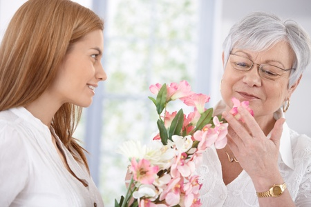 Pretty woman greeting her mother at mother's day, giving flowers, both smiling.