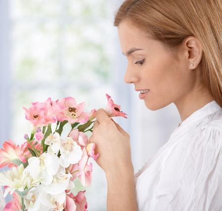 Beautiful young woman smelling flowers.