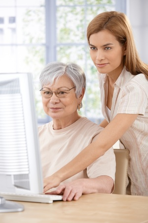 Mother and adult daughter browsing internet at home on computer.