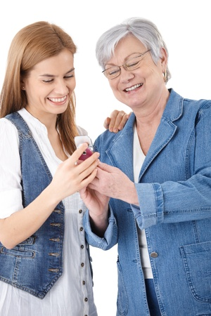 Senior mother and attractive young daughter looking at photos on mobile phone, smiling happily.